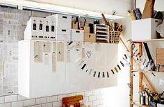 Weiße und birkenfarbene Boxen und KVISSLE Zeitschriftensammler in Weiß über einem weißen Küchenschrank