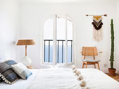 White bedroom with a sea view in a beautiful bohemian retreat in Marseillebelonging to Emma Francis (Sessun). Photography - Herve Goluza for Glamour France.
