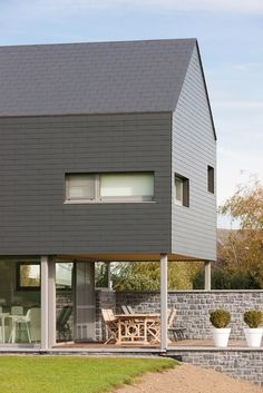 Our fibre cement Vertigo slates beautifully enveloping both the roof and facade. Fabric Awning, Retractable Awning, Build Your Own House, Slate Roof, Pink Houses, Cladding, Windows And Doors, Facade, Beautiful Homes