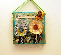 """This cute mini mixed media original art on canvas has yellow flowers with beaded jeweled centers and chevron stems. The art reads """"You are Everything"""" making it great for Valentine's day or another special occasion. The colorful collage art painting has a bright yellow butterfly and a chartreuse green ribbon to hang it on a wall or from a kitchen cabinet knob or a dresser knob. The petite size also makes a great desk ornament. This makes a creative gift for women of all ages whether for a…"""