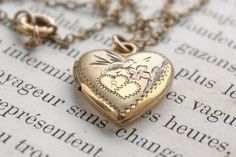 1940s sweetheart locket necklace with matching expansion bracelet features a little pink bird fluttering toward a pink flower. A sentimental piece of
