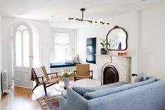 Modern living space with a vintage front door, a fireplace, a modern light, and a blue sofa