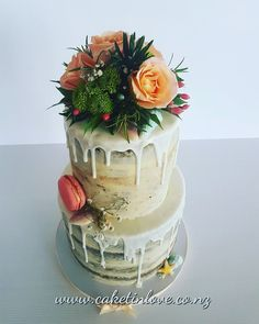 A gorgeous semi naked carrot cake with fresh flowers, macaroons and chocolate shells