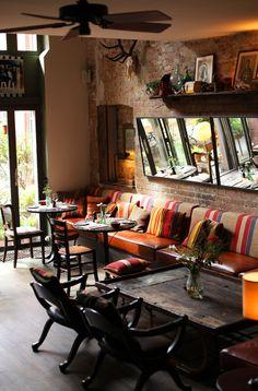 Sofá Baú com mesas e cadeiras. Prateleiras e espelhos. Iluminação natural e indireta artificial.