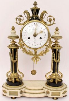 """French gilt bronze and alabaster mantel clock with circular white enamel clock face with hand painted pink flowers alternating with black numbers marked """"Bartemann a Paris"""" behind hinged glazed door below black slate urn form topped by acorn finial and flanked by birds with scrolled foliate bodies and draped chain held in mouth. Leaved and floral swag with ribbon below clock face. Sold for $2,360"""