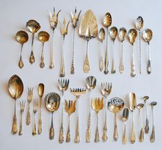 Antique Silver Flatware 1880-1910. TOP ROW: Cream ladles, lettuce forks, pastry server and olive spoons. BOTTOM ROW: Berry spoon, lemon forks, horseradish spoon, nut scoop, sardine forks, bonbon server, cheese scoops and mustard spoons.