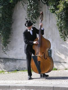 (he's weird-looking but...) Like this, standing. Or on bar stool. (Bass violin)
