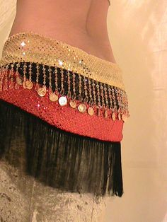 Belly dance Hip scarf in shimmering gold, red and black with amber beads, fringe and gold coins. $49.49, via Etsy.
