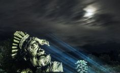 Many times larger than life, the faces of indigenous Brazilian people illuminate the darkened Amazon Rainforest, projected directly onto the trees as a symbolic representation of their connection t…