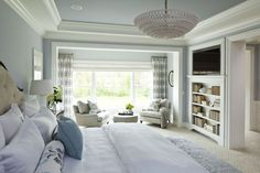 Expansive elegant master bedroom with carpet and blue walls gray sofa and pillow throws chandelier lamp geometric curtains wall mounted TV of Creative Design for the Best Paint Colors with Oak Trim in Your Vivid Rooms