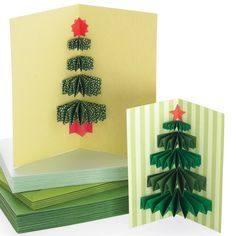 As this Christmas card opens, a 3-D tree made from pleated paper rectangles pops out, like a small gift. Although it can be glued into any size greeting, it is especially attractive in a tall, slender card that mimics a pine tree's natural dimensions.