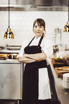 Portrait of confident female chef standing arms crossed in a commercial kitchen