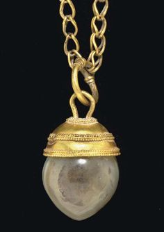 A SYRIAN GOLD AND BANDED AGATE PENDANT   CIRCA 1700 B.C.   The oval agate bead with a pointed tip; threaded by a plain gold wire loop to a hemispherical cap of thin sheet gold embellished with three bands of double rows of granulation flanking a plain wire, looped to a ring of plain wire, its tapering ends overlapping and wrapped spirally around itself; joined to an ancient-style gold loop-in-loop chain  1 5/8 in. (4.1 cm.) long