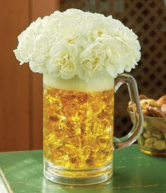 centerpiece idea- find cheap mugs, fill with gold wrapping paper, and top with carnations (or fake flowers).  Possibly wrap with a blue ribbon?