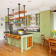 Not the green cabinets, but the ceiling -mounted shelving. DIYable with pipe and wooden frames with sturdy screening.