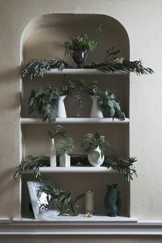 An alcove filled with white ceramics and winter greens, by J+G Design
