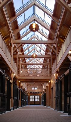 This timber frame horse stable in Massachusetts features a long clearstory allowing plentiful natural light into the facility.
