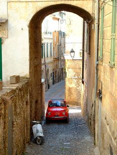 fiat and vespa, crumbling walls, narrow streets- there's no ambiguity that this is a still life portrait of Italy.