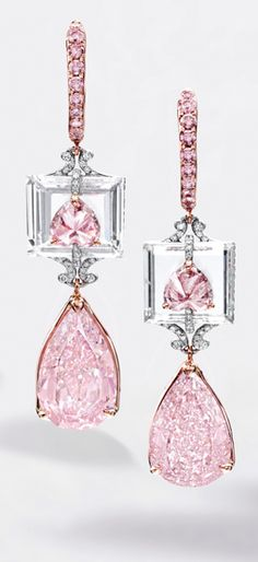 Fancy Intense Purplish-Pink Diamond and Diamond Pendent Earrings Suspending a pear-shaped fancy intense purple-pink diamond weighing 4.01 carats and a fancy intense purplish-pink diamond weighing 3.72 carats, surmounted by an inverted heart-shaped fancy purplish pink and fancy intense pink diamond weighing 0.63 and 0.55 carat respectively, to a step-cut diamond background altogether weighing approximately 5.05 carats, mounted in 18 karat white and pink gold.