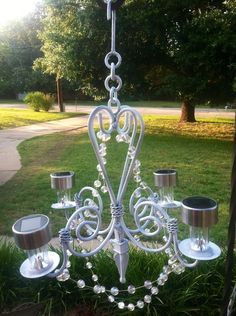 My homemade outdoor glitzy solar chandelier. Cut off stems of dollar store solar lights. Hot glue to vintage chandelier, add beads....instant garden glam!!!