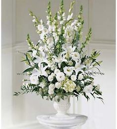 A brilliant display of white flowers to send your condolences. White lilies, white gladiolus and white lisianthus are accented with stock, snapdragons and more in a ceramic urn. Appropriate to send to a home or to a funeral.