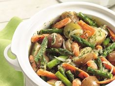 Enlist your slow cooker for a delicious fresh vegetable-packed side. Here, Dijon, lemon and dill brighten asparagus, baby carrots and new potatoes.