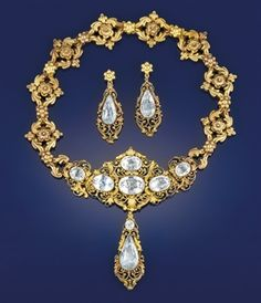 Gold and foiled aquamarine parure, c. 1840. Necklace of rosette and scroll openwork links suspending a central section of similar decoration composed of six oval foiled aquamarines with matching articulated shoulders each set with a single aquamarine, suspending a matching pendant drop, with additional spare drop, and a pair of earrings en suite.