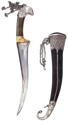 Indian pesh kabz, 19th c, recurved blade  with T-shaped spine profiled and engraved with an armory designation, raised central ridge at the armor-piercing tip,  hardstone grip with fine silver pommel in the form of a falcon and a festoon of silver chains with jingles, velvet-covered wooden scabbard with elaborately silver mounts, locket with silver binding chains engraved in geometrical and floral patterns, with a lion hunting its prey and a Hindu goddess worked on the chape,  length 36.5cm.