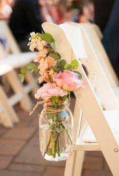 Rustic flower idea - jam jars of freshly cut garden flowers tied with string to chairs