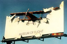 A billboard advertisement for the Museum of Flight in Seattle has a 3D plane crashed into the billboard and the only other words on the billboard are the name of the Museum.
