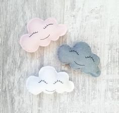 Set of 3 gorgeously cute, smiling fluffy clouds!  Each adorable cloud is hand cut and handstitched using soft wool felt. They each have a beaming, happy face that is also handstitched using black cotton. Each cloud has white wool attached at the back for pinning, allowing you to hang your clouds exactly how you want them. You will receive 1 grey, pink and white cloud Each cloud is approx 4 inches/10cm wide.  As all our items are made to order, if you require more clouds or different colo...