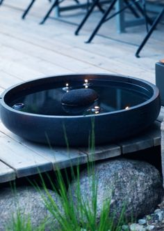 The evocative black birdbath  in concrete has been joined by a black lava stone from Bali and some floating candles on the terrace | garden of garden designer Anders Mårtensson