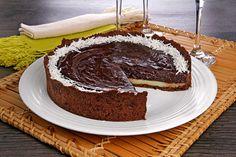 Torta de chocolate com coco em um prato de servir branco com um pedaço já retirado.