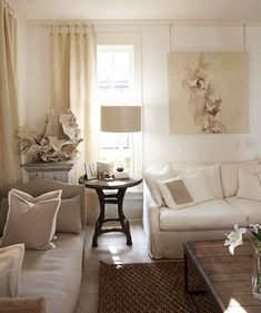 Natural, sand colors create a casual, comfortable living room. Linen fabrics keep the room casual. Large coral sculpture creates texture and interest. And we love how this designer hung the artwork from the molding, using rope, to keep within the natural, neutral theme.