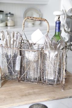 french wire bottle carrier holding flatware, napkins and wine. Debra Hall Lifestyle: French at Home Silverware Caddy, Flatware Storage, Cutlery Holder, Bottle Carrier, Farmhouse Chic, Farmhouse Ideas, Wire Baskets, Kitchen Decor, Cozy Kitchen