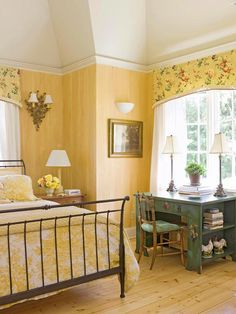 Butterscotch tones add warm brown notes to this charming and traditional bedroom where color and paint create character in a small space. The rich yellow walls are painted to mimic wide wooden boards, while yellow and ivory toile linens, yellow chintz valance, golden sconces, and the bold contrast of an iron bed combine to produce a look that¿s simple yet sophisticated.