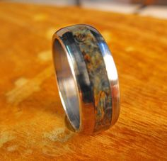 This titanium ring is one of our custom made rings that weve hand sized and milled, then inlaid with some gorgeous black ash burl. We were so excited
