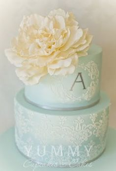 Wedding cake in soft blue and cream with a large beautiful bloom and extensive piping design.