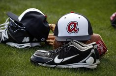 A new style Atlanta Braves hat sits on a glove during a spring training workout, Thursday in Lake Buena Vista, Fla. Pitchers and catcher must report by Friday.