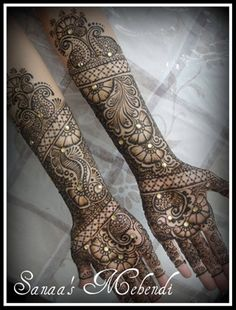 Henna Design with Crystal Gems     Two arms filled with mehndi and decorated with gems.