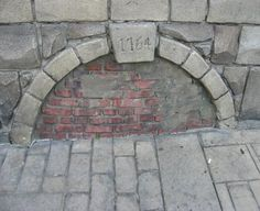 "This always puzzles guests - why is there a bricked over archway with the date 1764? The answer to the mystery lies in plans that never were realized. Plans for a walkthrough cavern and tunnel connecting New Orleans Square and Tom Sawyer's Island. The ""plot"" being that a pirate who owned the Haunted Mansion for a time had buried treasure underneath the river and sealed up the entrance with bricks and a curse… Unfortunately the planned update never happened, but this brick remains."