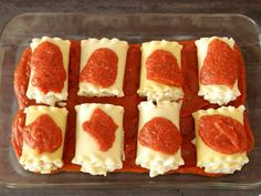 This photo shows lasagna rolls in a baking pan with marinara sauce on top