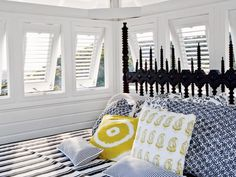 Soft and hard elements combine in this St. Barts bedroom, defining the luxurious simplicity of West Indies style. The homeowners chose a restrained palette of black, white, yellow, and blue that rests against large white shuttered windows. A dramatic modern Gothic headboard stands out against the peaceful space.