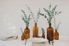 CENTRO DE MESA con botellas color ambar y ramas de eucalipto #ideas