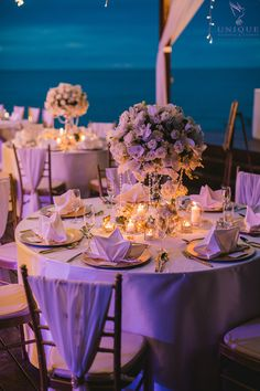 Reception tables decorated with gold tiffany chairs and gold charger plates with candles, flowers and gold gems