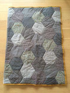 Så blev mit første sekskant tæppe færdigt. Det er lavet i grå nuancer, stof fra stof&stil og med gul kant. Tæppet er syet på maskine.