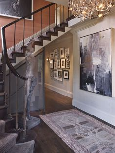 I love this transitional space--the main art work, the color above the stairs, the statue and the collage on the wall.