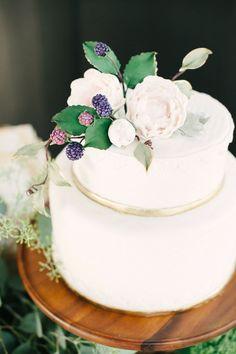 Witte bruidstaart met bloemen en goud accent