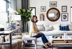 Erica Chan Coffman's cosy living room features neutral coloured furniture, a large window streaming natural light and a galley wall with a  selection of prints and a mirror