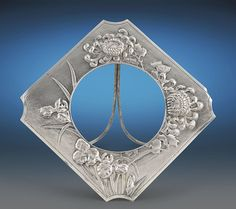 This elegant and unique Chinese export silver frame boasts a charming motif and exceptional craftsmanship, qualities for which Chinese export silver is renowned. The enchanting piece is beautifully handcrafted in an exquisite chrysanthemum and orchid pattern over the fine matted ground. The stunning form is distinguished by its delicately curved corners, which lend the frame a sophisticated elegance that would enhance any mantle.<br><br>This charming piece bears the mark of Wang Hing